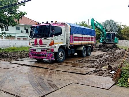 รถบรรทุกสิบล้อ ขนดิน บนแท่นรับดิน มีแมคโครช่วยรับดิน